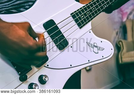 9/20/2020 - New York, Ny: Bass Guitar Playing With A Pick In Hand. Practicing And Creating Bass Riff