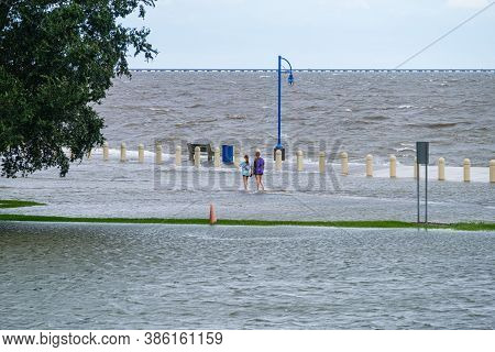 New Orleans, Louisiana/usa - 9/15/2020: Two Girls Wading In Flooded Street Along Lake Pontchartrain