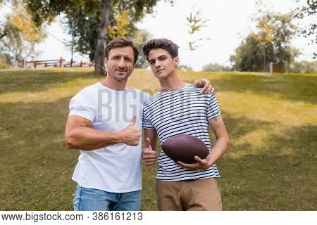 Father And Teenager Son With Rugby Ball Showing Thumbs Up In Park