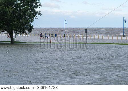 New Orleans, Louisiana/usa - 9/15/2020: Family Wading Along Lake Pontchartrain During Storm Surge Fr