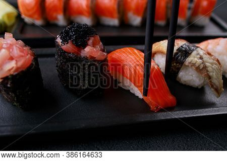 Eating Sushi. Chopsticks Taking Salmon Nigiri Sushi From Plate. Japanese Food, Deluxe Restaurant Men