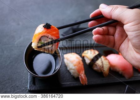 Eating Sushi. Hand With Chopsticks Taking Salmon Maki Roll From Plate. Japanese Food, Deluxe Restaur