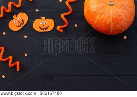 Orange And Black Halloween Flatlay. Pumpkins From Felt And Real Pumpkin On A Black Wooden Background
