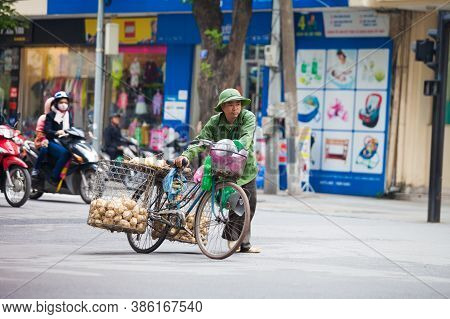 Hanoi, Vietnam - November 21, 2019: Street vendors are hurriedly cycling across the street to find c