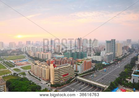 buldings, road with overhead crossing, cars, busses in sunrise in Guangzhou, China poster