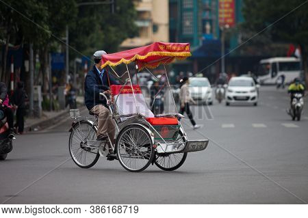 Traditional cyclo ride down the streets of Hanoi, Vietnam. The cyclo is a three-wheel bicycle taxi t