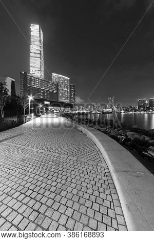 Seaside Promenade And Skyline Of Hong Kong City At Night