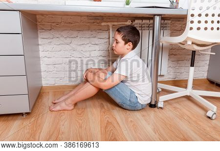 Unhappy Kid Boy Sitting Under Desk. Teen Feeling Anxious. Child Suffering From Loneliness. Junior Hi