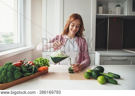 Caucasian Woman With Freckles And Red Hair Is Putting Fresh Green Juice In Glass Squeezed From Veget