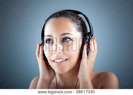 Image of beautiful young woman listening to music with headphones