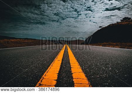 Perspective View Of Yellow Lane Lines Of An Old Asphalt Road Through The Field And Clouds On Blue Sk