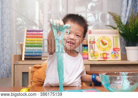 Cute Happy Smiling Asian 4 Years Old Kindergarten School Boy Having Fun Making Fluffy Slime, Young K