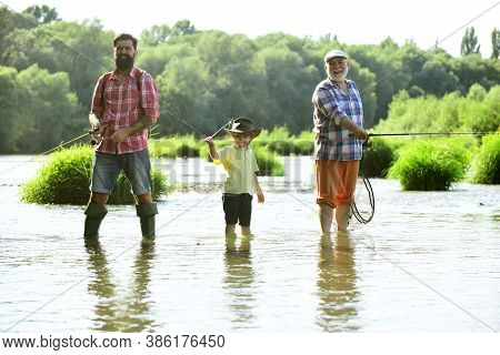 Grandfather, Father And Grandson Fishing Together. Fishing. Happy People Family Have Fishing And Fun