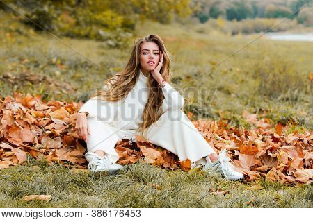 Woman In A Autumn Park. Caucasian Girl In A Sweater Walking Outdoors. Fashion Portrait Stylish Prett