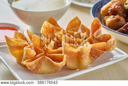 chinese crab rangoon fried wontons on plate with red sauce