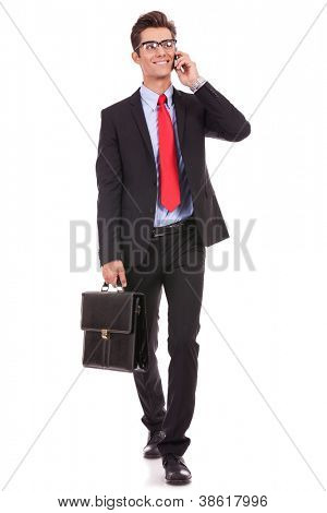walking young business man with briefcase , looking away from the camera while speking on his smartphone, isolated on white background