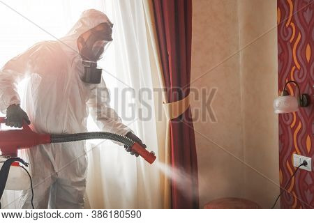 Pest Control Specialist In White Hazmat Contractor Working In Flat And Hotel