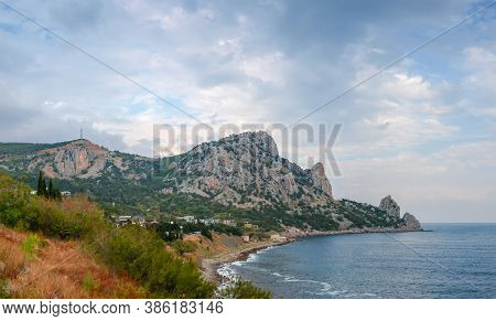 Mountain With Limestone Rocky Outcrops Covered With Rare Grown Trees On The Coast Of Sea Against The
