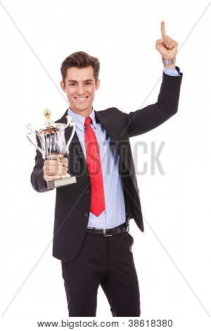 Happy business man holding a trophy aloft over white
