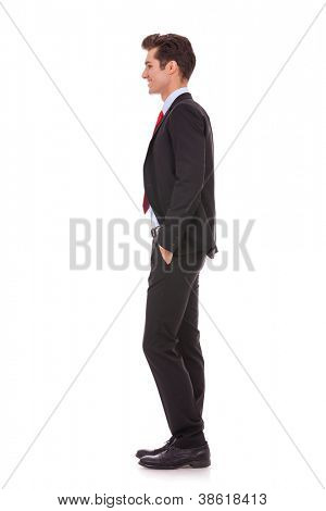 Stock photo of the side view profile of a well dressed business man smiling. Full length, isolated white.