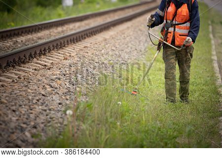 A Front View Of A Worker In Protective Clothing Walks Along The Lawn Next To The Train Tracks And Mo