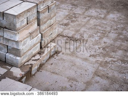 Laying And Repairing Paving Slabs At A Construction Site On A Walkway, Against A Background Of Stack