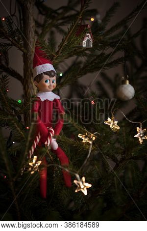 A Cute Christmas Toy Sits On An Evergreen Fir Tree Decorated With Garlands And Other New Years Toys,