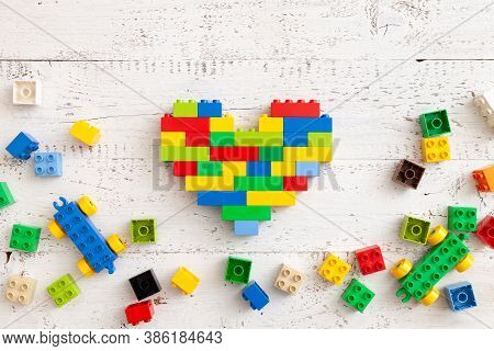 Multi-colored Plastic Cubes Are Scattered On A White Wooden Table. Top View Of A Multi-colored Heart