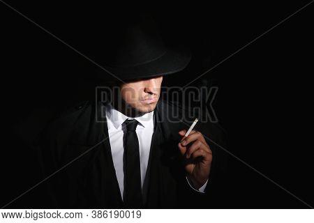 Old Fashioned Detective Smoking Cigarette On Dark Background