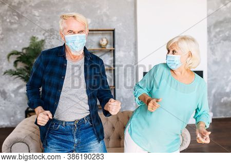 Positive And Cheerful Senior Couple Wearing Medicine Masks Has Fun Together At Home During Quarantin