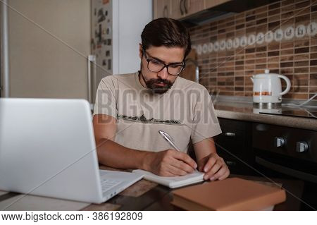 Concentrated Millennial Hipster Guy Wearing Glasses, Listening To Favorite Music While Planning Work