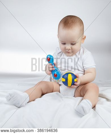 Photo Of A Ten-month-old Choosing Baby Between Rattle And Ball