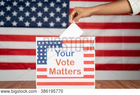 Close Up Of Hands Placing Vote Inside The Ballot Box With Your Vote Matters Printed With Us Flag As