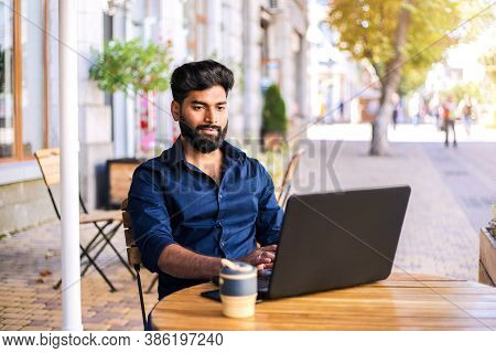 Young Successfull Businessman Working In Cafe Outdoors In The Autumn.