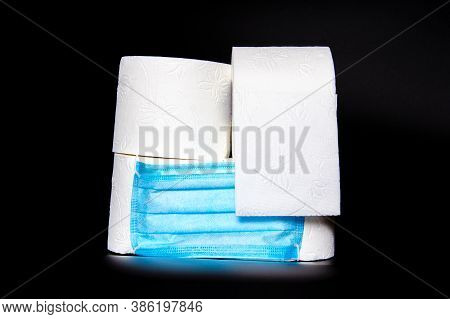 4 Rolls Of Toilet Paper With A Medical Facial Mask. One Roll Started, On A Black Background. Quarant