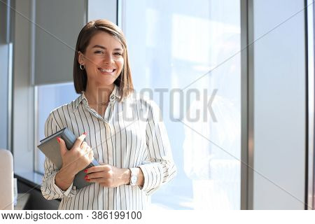 Attractive Business Woman Looking At Camera And Smiling While Standing In The Office.