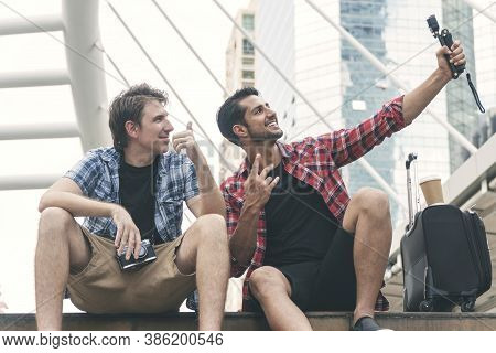 Two Blogger Handsome Friends Taking Selfie Together With Action Camera Sitting On Street City Lookin
