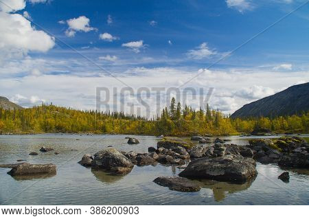 Misty Morning On A Small Mountain Lake With A Scattering Of Boulders, Reflecting Dense Clouds, Surro