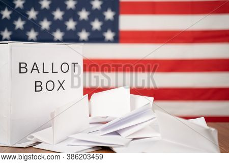 Ballot Box With Votes On Table Before Counting With Us Flag As Background Concept Of Ballot Or Vote