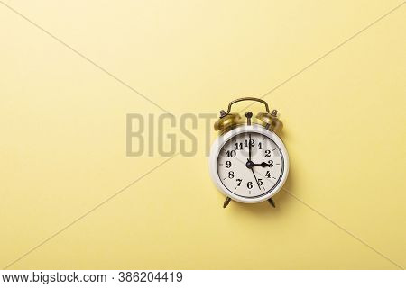 Concept Of Daylight Saving Time. Retro Clock On The Yellow Background. Top Down View With Copy Space