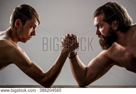 Arms Wrestling Thin Hand, Big Strong Arm In Studio. Two Mans Hands Clasped Arm Wrestling, Strong And