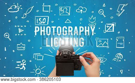 Hand taking picture with digital camera and PHOTOGRAPHY LIGHTING inscription, camera settings concept
