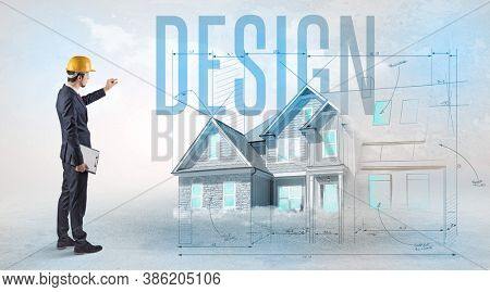Young engineer holding blueprint with DESIGN inscription, house planning concept