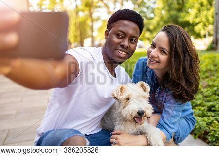 Happy young couple with their pet dog outdoors