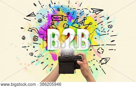Close-up of a hand holding digital camera with abstract drawing and B2B inscription