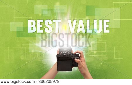 Close-up of a hand holding digital camera with BEST VALUE inscription, traveling concept