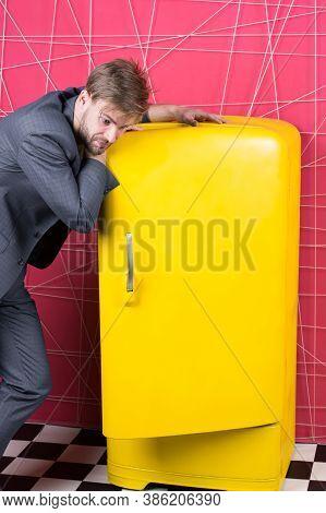 Man Formal Elegant Suit Stand Near Retro Vintage Yellow Refrigerator. Vintage Household Appliances.