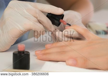 Woman Manicurist Master Is Applying Pink Gel On Clients Nails In Beauty Salon, Hands Closeup. Manicu