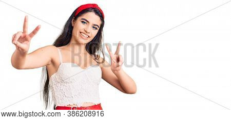 Brunette teenager girl wearing elegant look smiling looking to the camera showing fingers doing victory sign. number two.