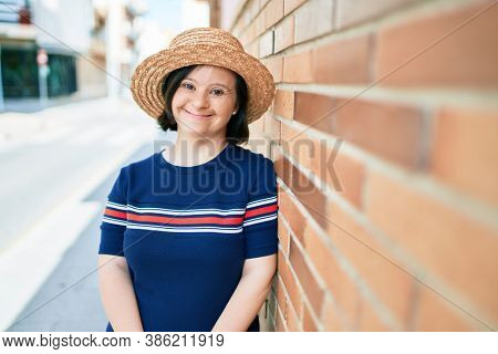 Beautiful brunette woman with down syndrome wearing a summer hat at the town on a sunny day leaning on a bricks wall